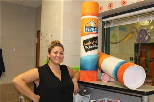 Sara Felt stands by several of her classroom art decorations - larger than life glue