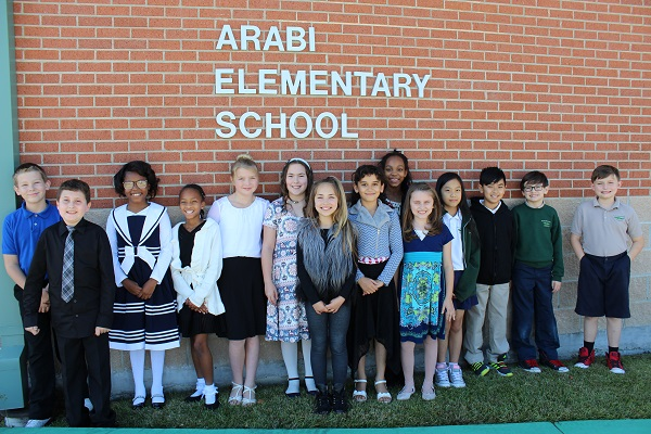Students dressed in nice outfits standing in front of the Arabi Elementary School building